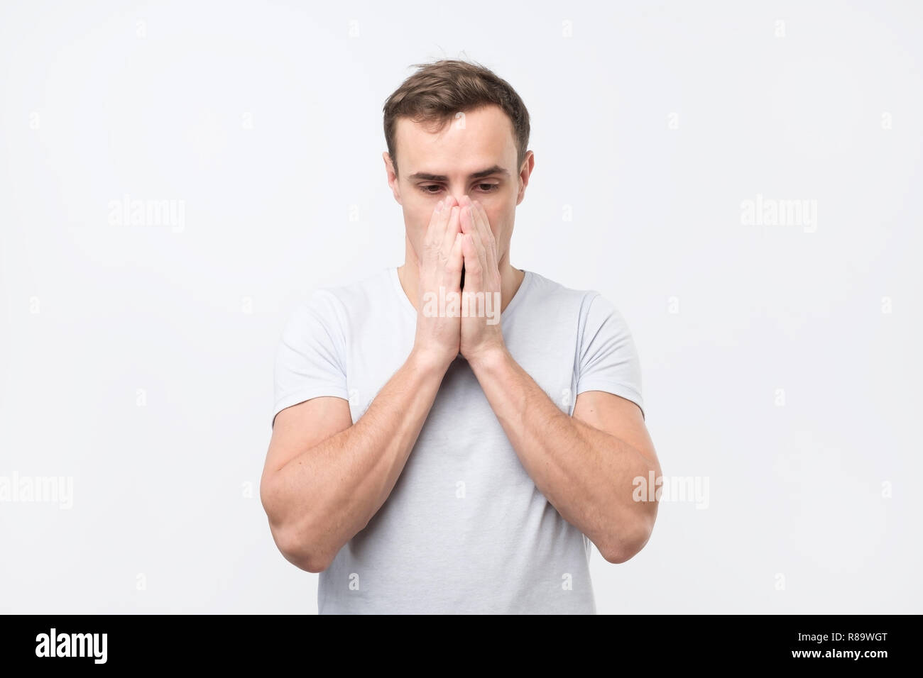 Young tired, fatigued man with worried face, stressed, dragging face down with hands. - Stock Image