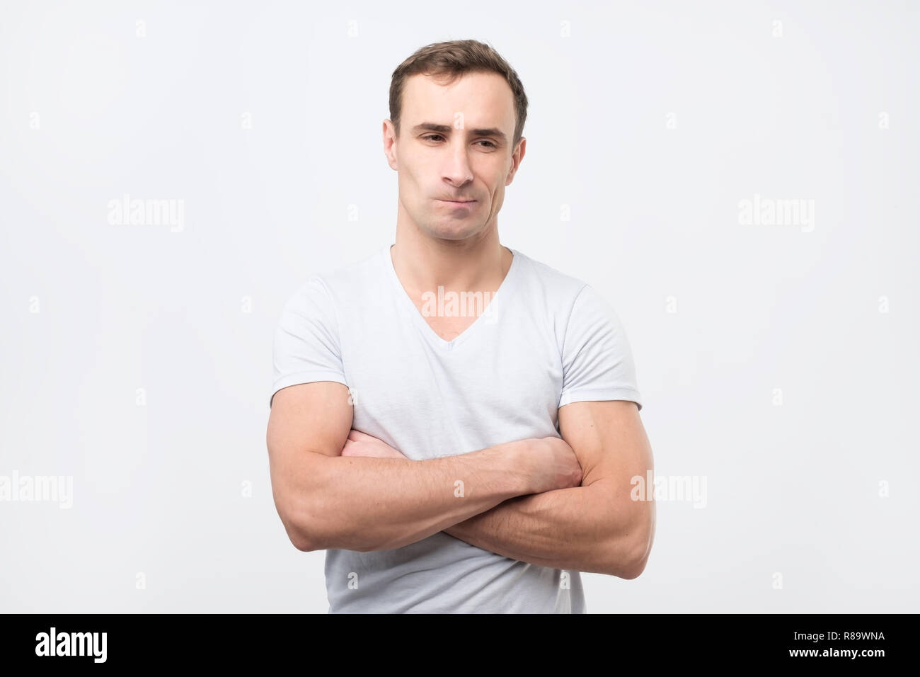 Sad italian guy in white t-shirt thoughtfully looking aside - Stock Image