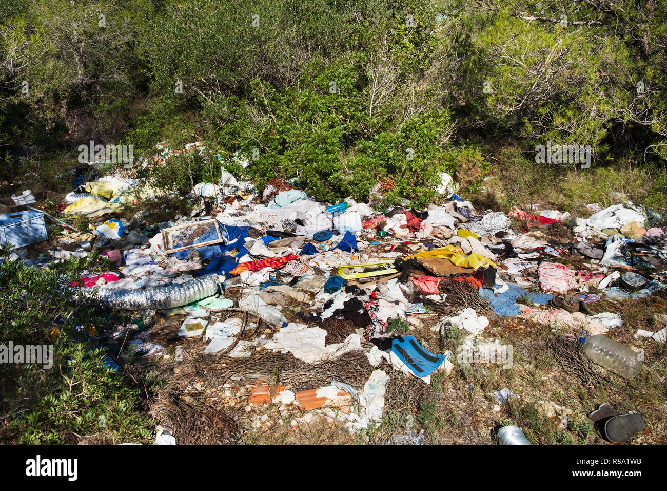 view of a pile of garbage illegally dumped in an open dump by a rural lane - Stock Image