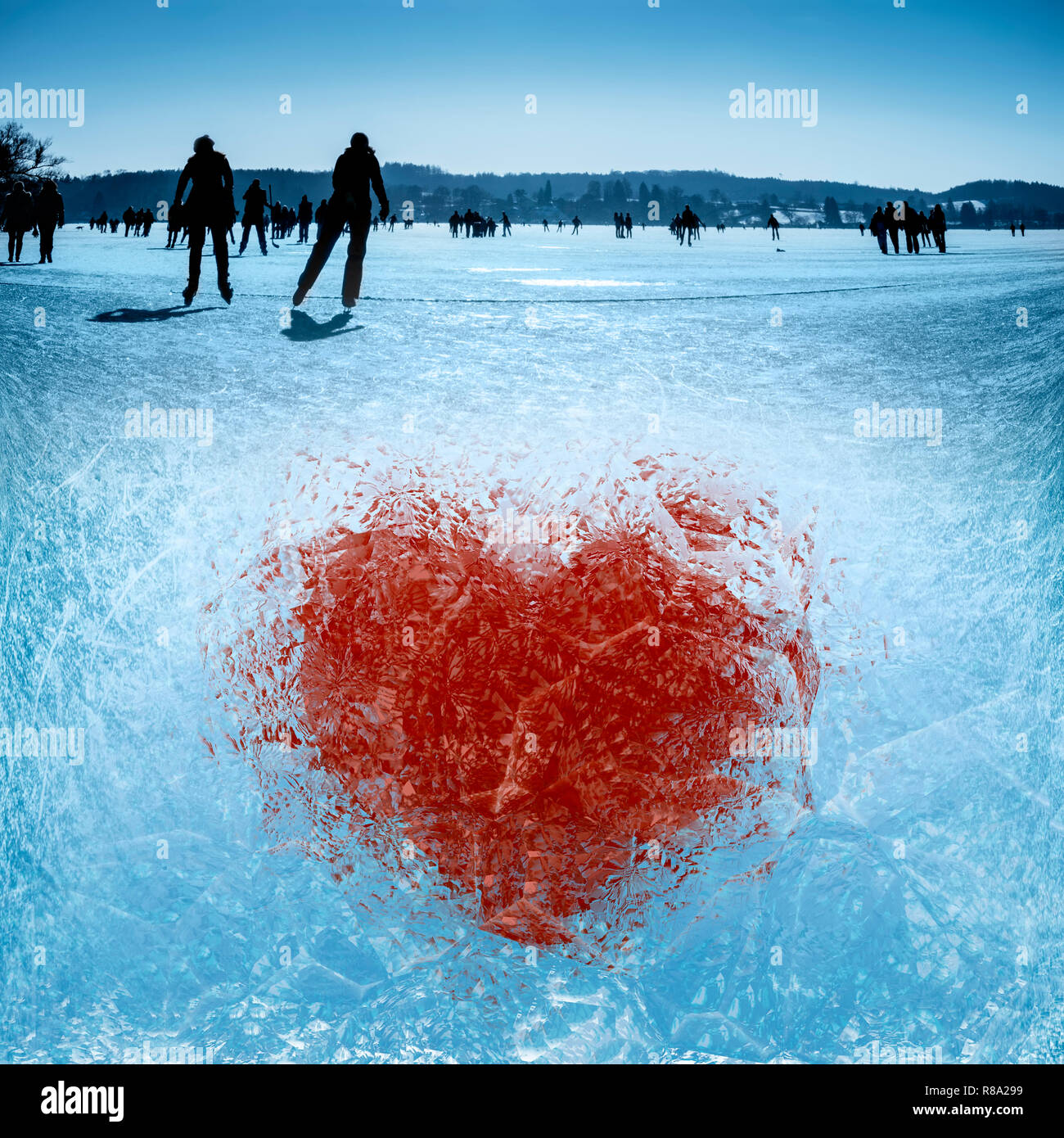 Ice-frozen heart on a lake with skaters - Stock Image