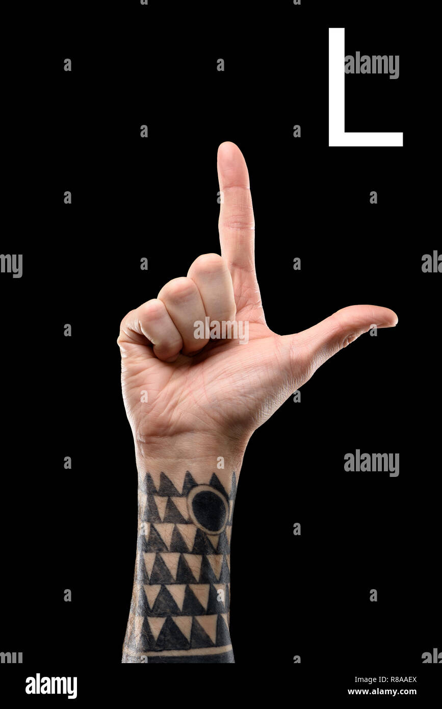 Cropped view of tattooed hand showing latin letter l sign language isolated on black