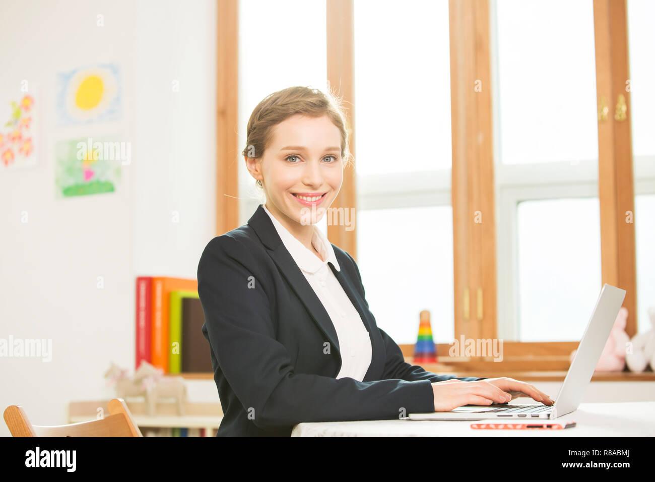 Foreign Female Teacher At Her Desk - Stock Image