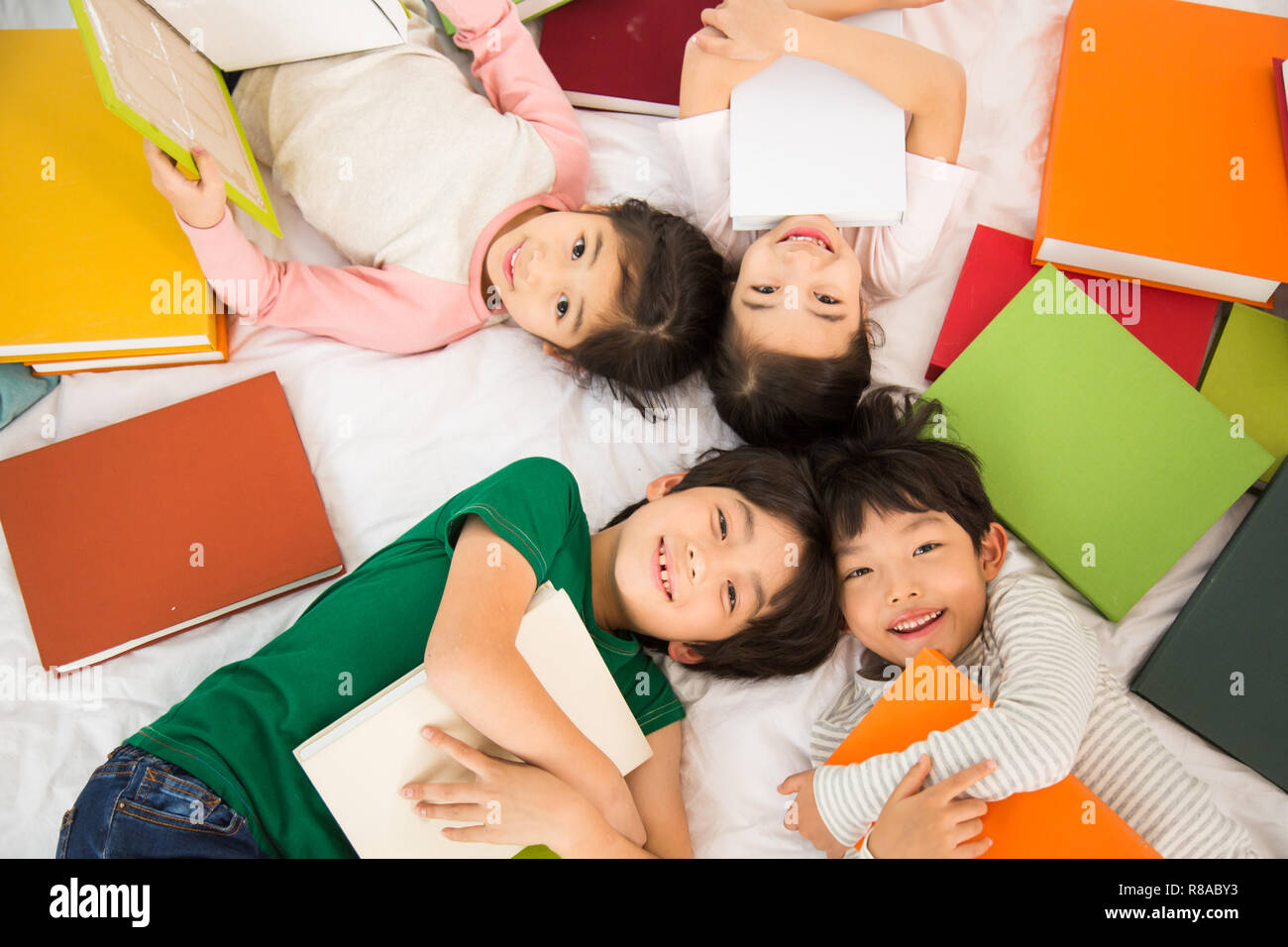 Young Students Lying On Their Backs With Piles Of Books - Stock Image
