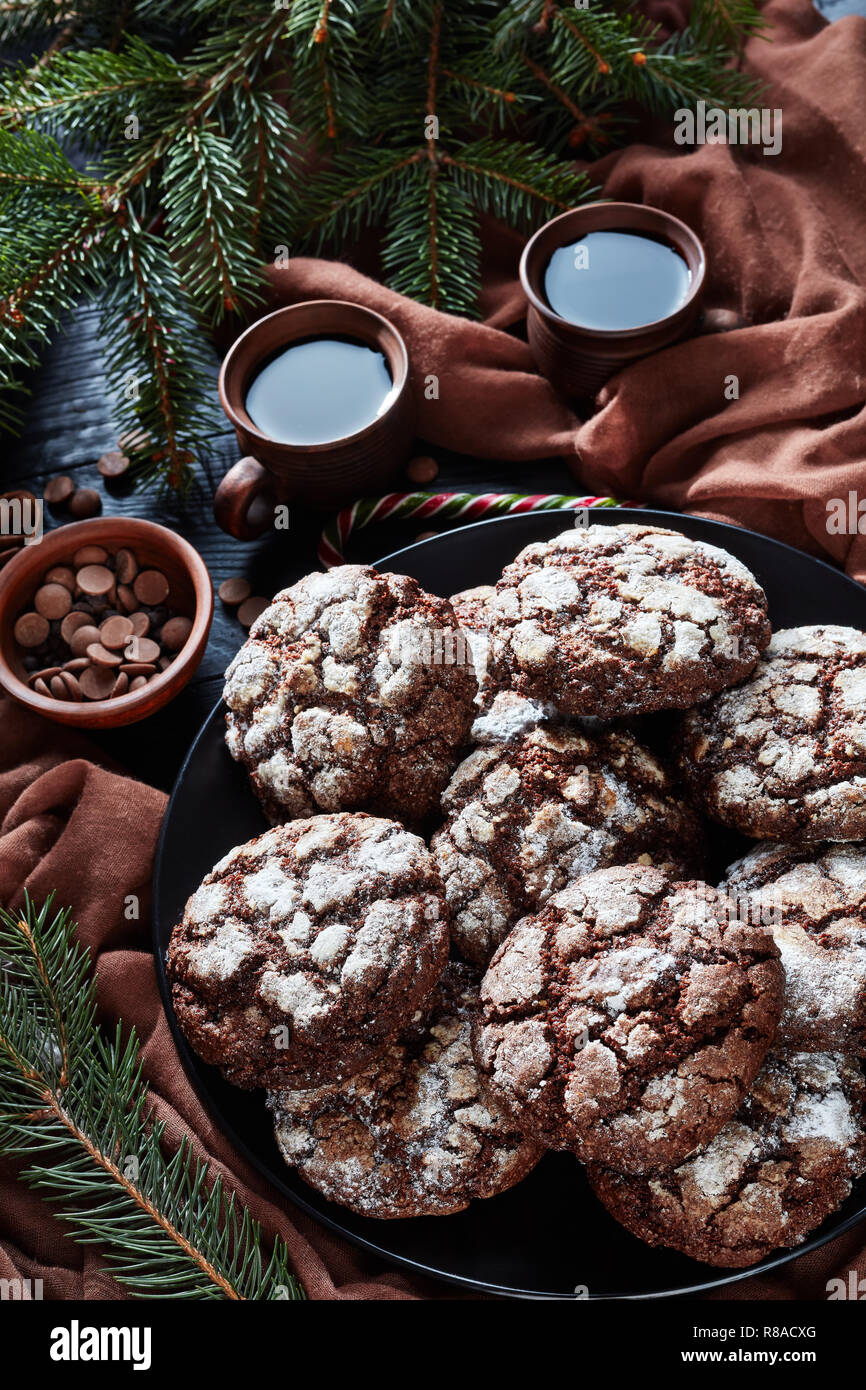 close-up of Christmas Chocolate Crinkle cookies on a plate on a black wooden table with fir tree, candy canes, brown cloth and cups of coffee, rustic  Stock Photo