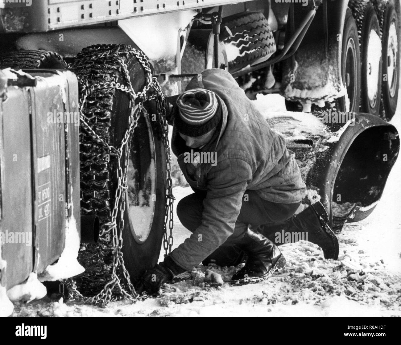 A truck driver pulls on his vehicle on January 3, 1979 on snow chains. The drop in temperature on December 29, 1978, led to snow chaos in northern Germany, the north of the GDR, Denmark, and southern Sweden. Partly the traffic and the power supply collapsed, localities were cut off from the outside world. In the Federal Republic alone, 17 people were killed because of the snow chaos. | usage worldwide - Stock Image