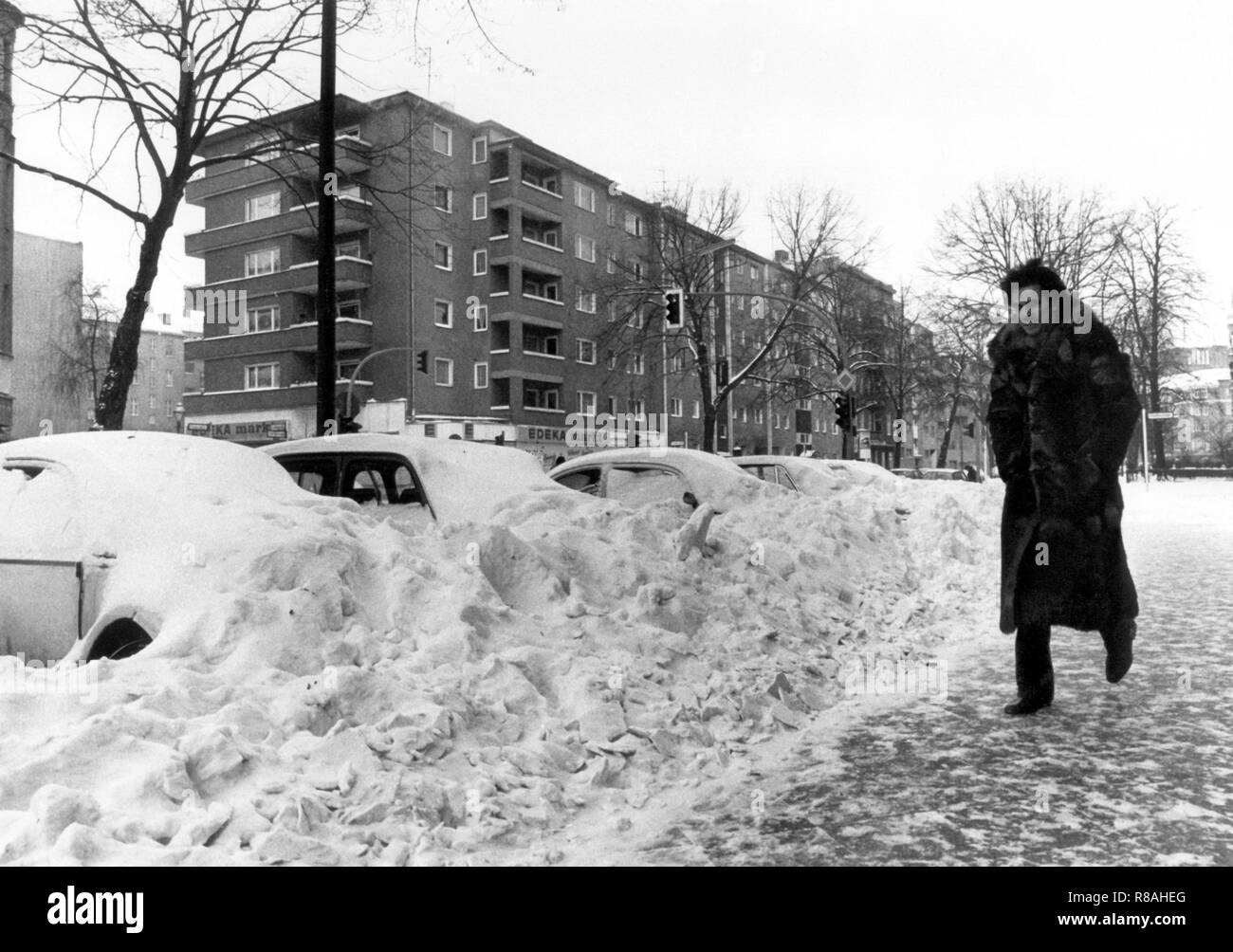 A pedestrian makes his way over the icy road, while the parked cars are almost covered by the snow, taken on 3 January 1979 in Berlin. The drop in temperature on December 29, 1978, led to snow chaos in northern Germany, the north of the GDR, Denmark, and southern Sweden. Partly the traffic and the power supply collapsed, localities were cut off from the outside world. In the Federal Republic alone, 17 people were killed because of the snow chaos. | usage worldwide - Stock Image