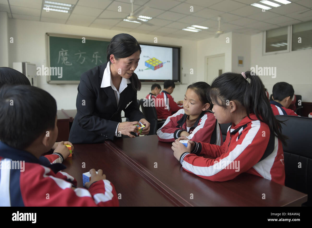 Gu'an, China's Hebei Province. 14th Dec, 2018. Students practise Rubik's Cubes under the guidance of a teacher at Nanzhaogezhuang primary school in Gu'an County, north China's Hebei Province, Dec. 14, 2018. Various extracurricular classes are provided in Nanzhaogezhuang primary school to enrich the school life of students. Credit: Lu Peng/Xinhua/Alamy Live News - Stock Image