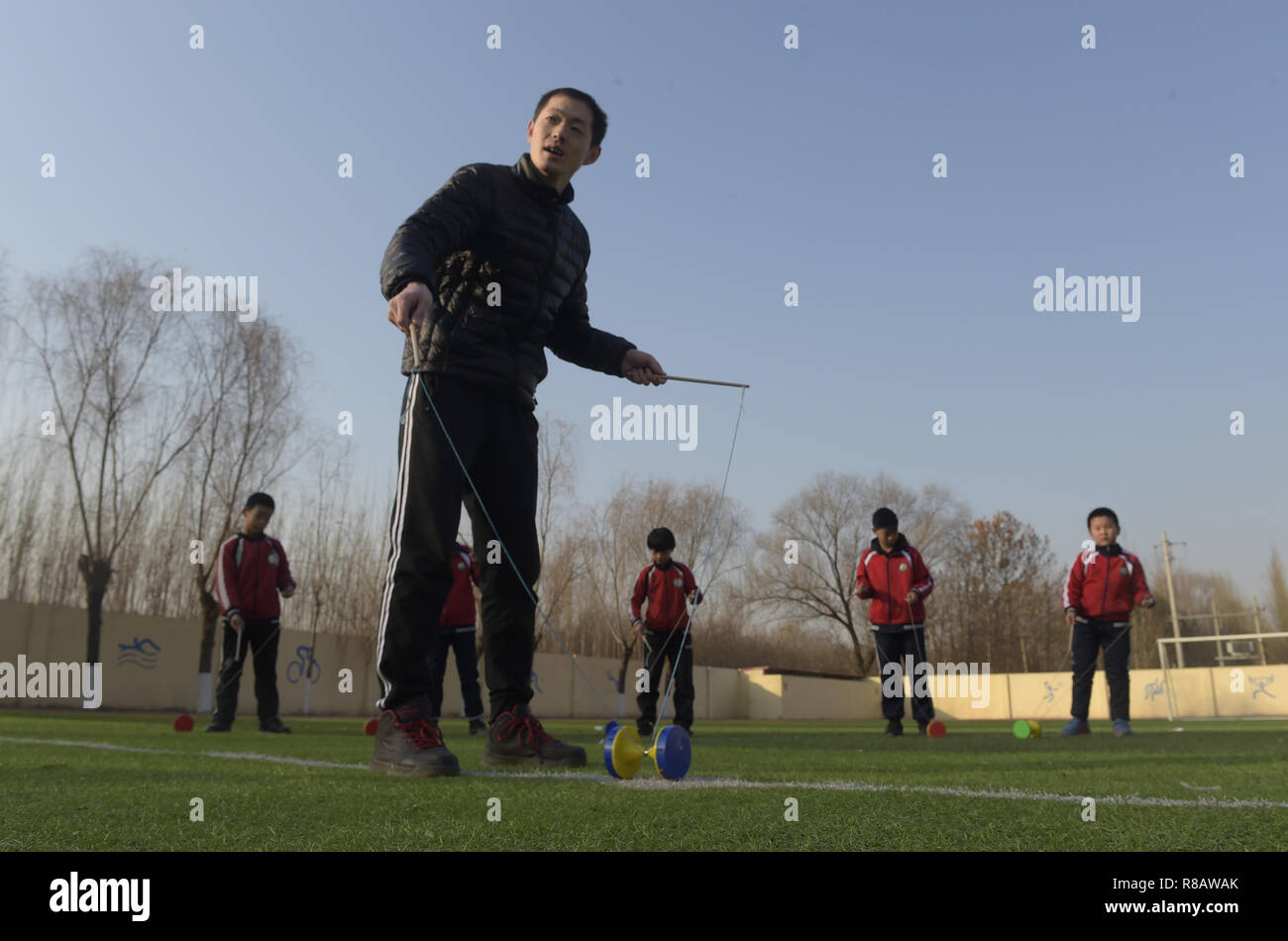 Gu'an, China's Hebei Province. 14th Dec, 2018. Students play diabolo under the guidance of a teacher at Nanzhaogezhuang primary school in Gu'an County, north China's Hebei Province, Dec. 14, 2018. Various extracurricular classes are provided in Nanzhaogezhuang primary school to enrich the school life of students. Credit: Lu Peng/Xinhua/Alamy Live News - Stock Image