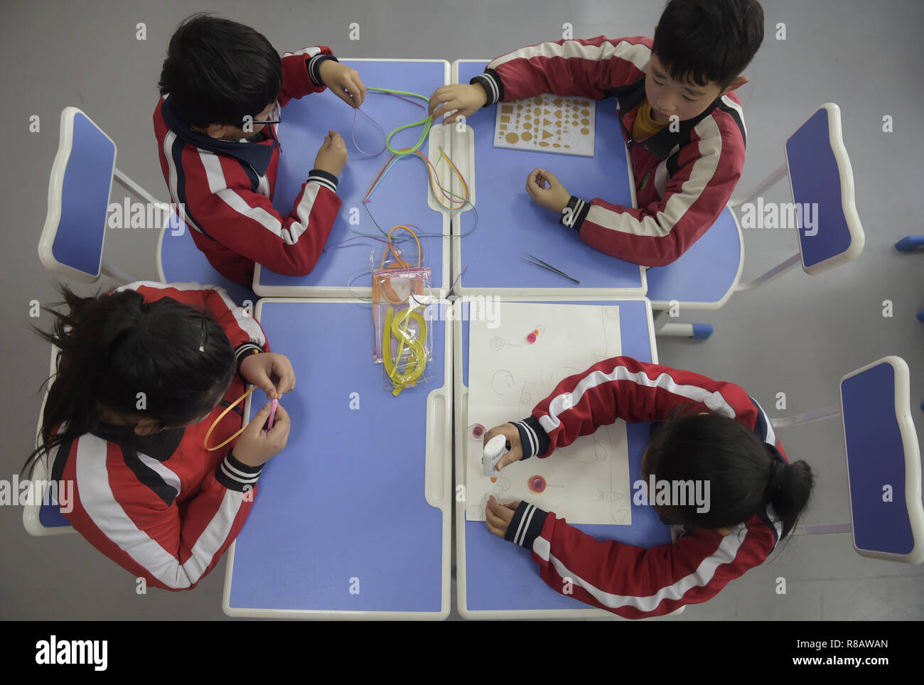 Gu'an, China's Hebei Province. 14th Dec, 2018. Students learn to make pictures by gluing colored materials at Nanzhaogezhuang primary school in Gu'an County, north China's Hebei Province, Dec. 14, 2018. Various extracurricular classes are provided in Nanzhaogezhuang primary school to enrich the school life of students. Credit: Lu Peng/Xinhua/Alamy Live News - Stock Image