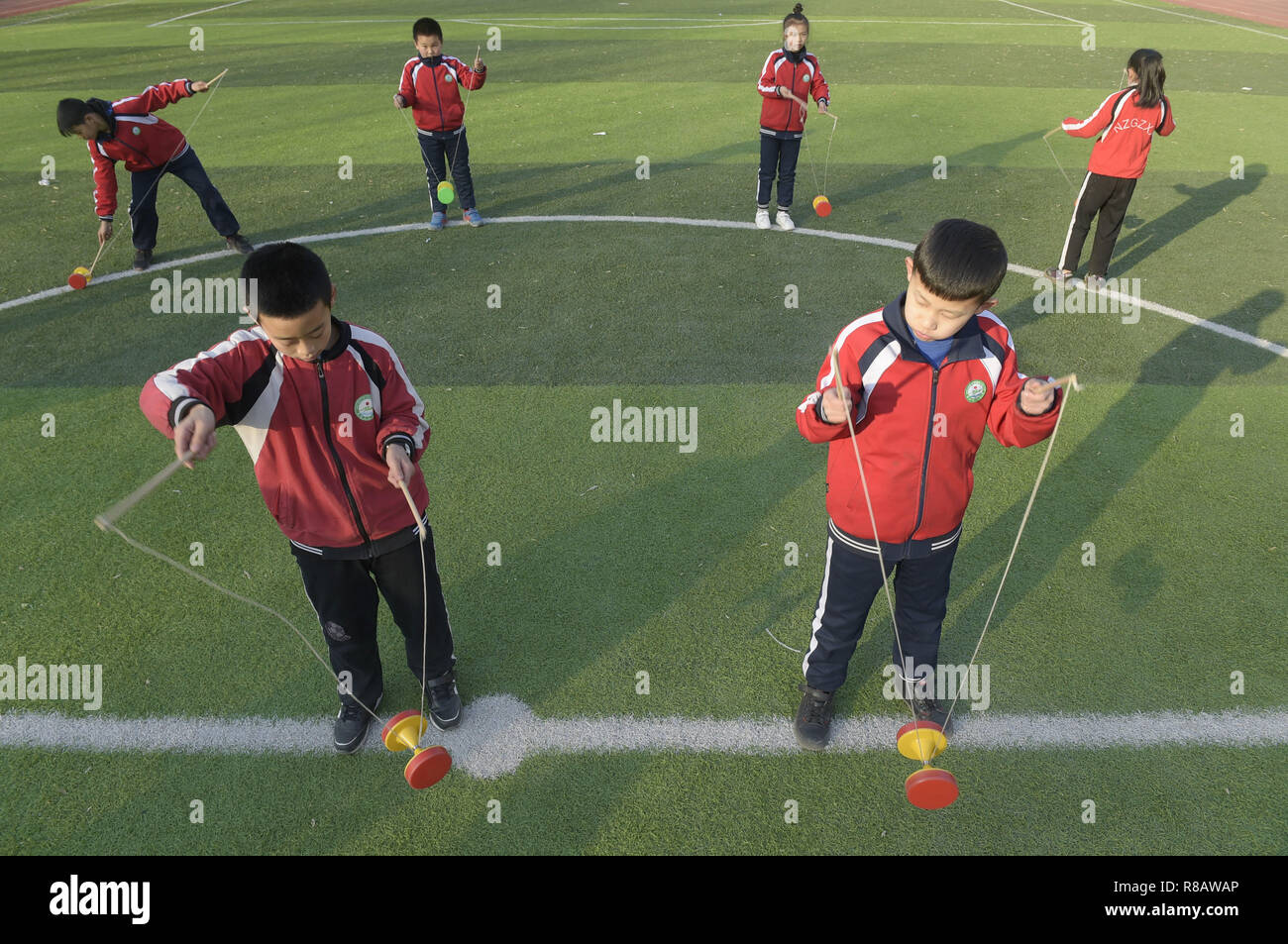 Gu'an, China's Hebei Province. 14th Dec, 2018. Students play diabolo at Nanzhaogezhuang primary school in Gu'an County, north China's Hebei Province, Dec. 14, 2018. Various extracurricular classes are provided in Nanzhaogezhuang primary school to enrich the school life of students. Credit: Lu Peng/Xinhua/Alamy Live News - Stock Image