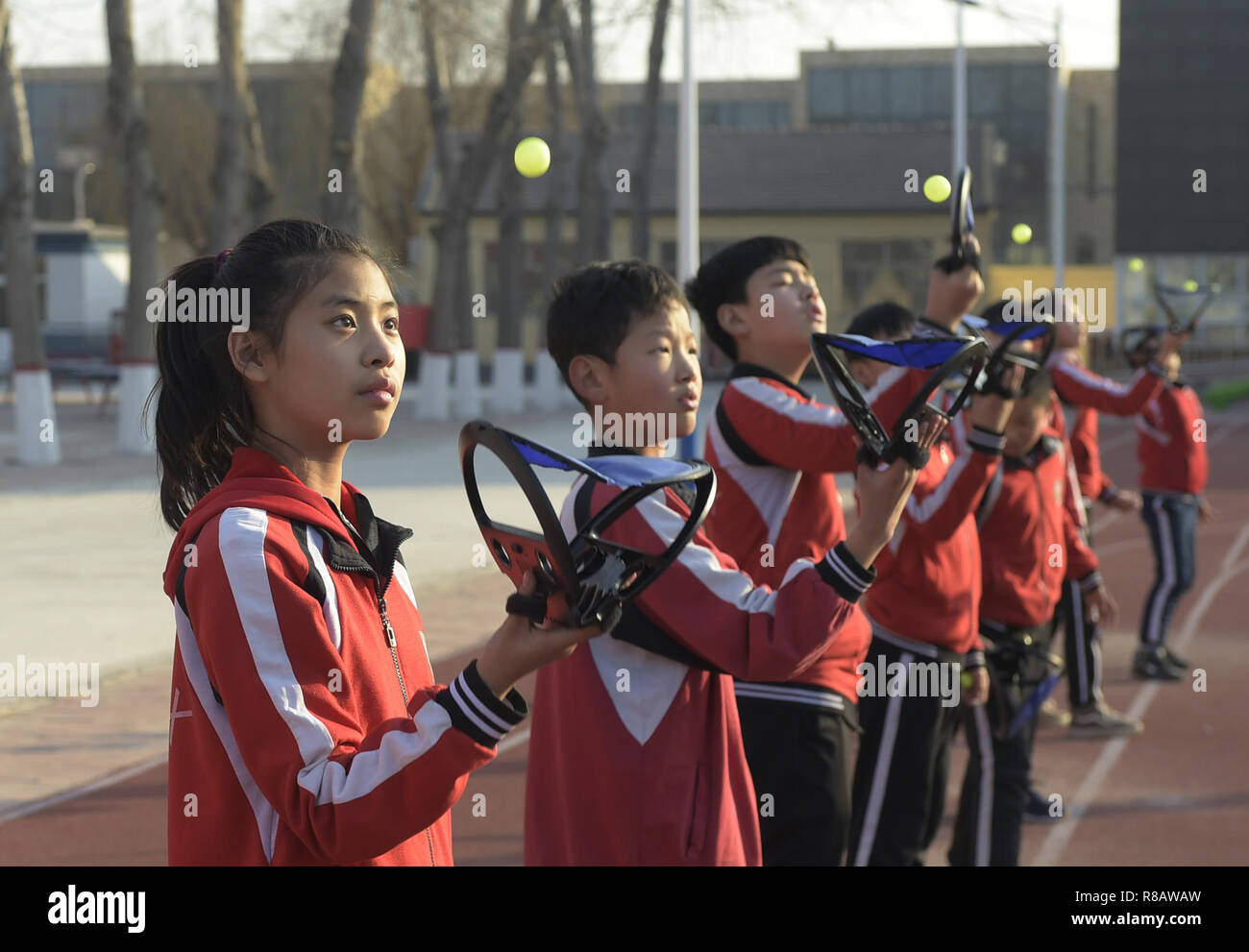Gu'an, China's Hebei Province. 14th Dec, 2018. Students practise catching balls at Nanzhaogezhuang primary school in Gu'an County, north China's Hebei Province, Dec. 14, 2018. Various extracurricular classes are provided in Nanzhaogezhuang primary school to enrich the school life of students. Credit: Lu Peng/Xinhua/Alamy Live News - Stock Image