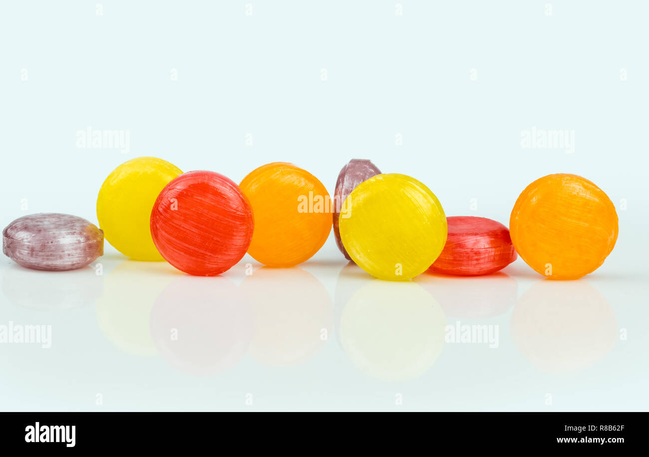 Medical lozenges for relief cough, sore throat and throat irritation isolated on white background. Cough and colds drop. Colorful cough pastille. Red, - Stock Image