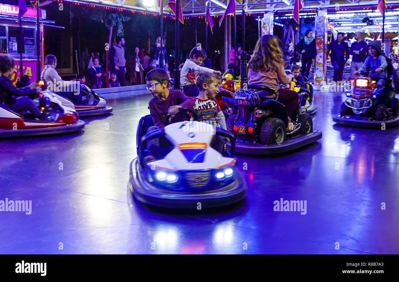 Kids in bumper cars at an amusement park in Seville, Spain - Stock Image