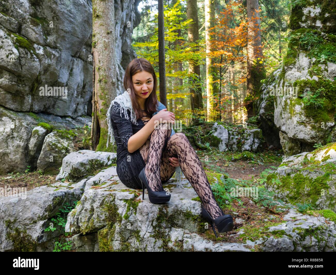 Beautiful young female in nature is sitting atop big rock looking at camera legs heels spike spiked model-released release Stock Photo
