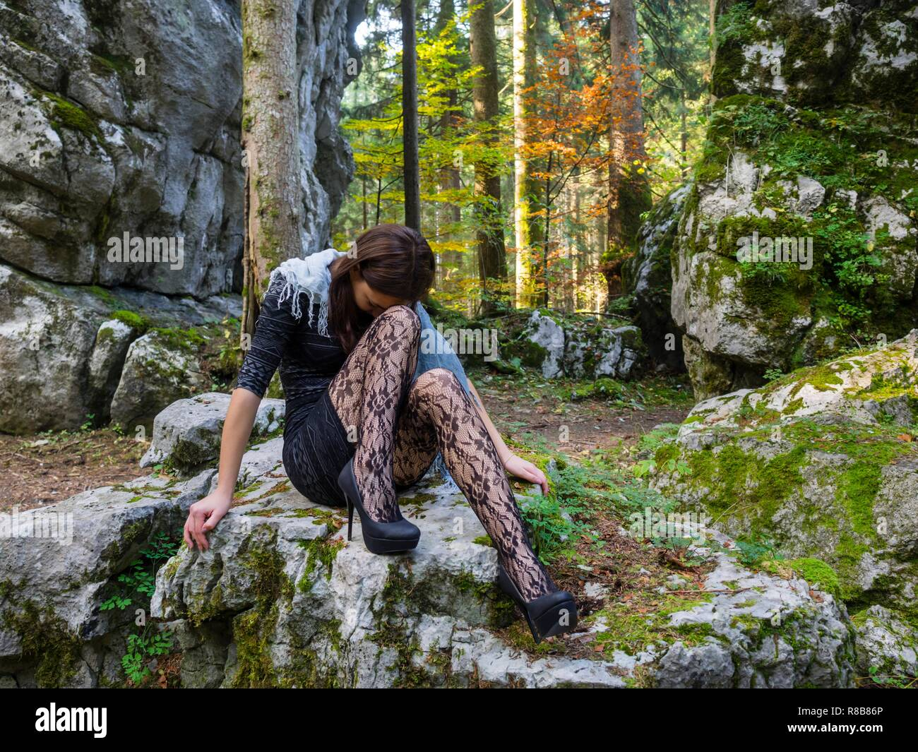 Beautiful young female in nature is sitting atop big rock in bad mood negative feeling concerned looking down hiding face - Stock Image