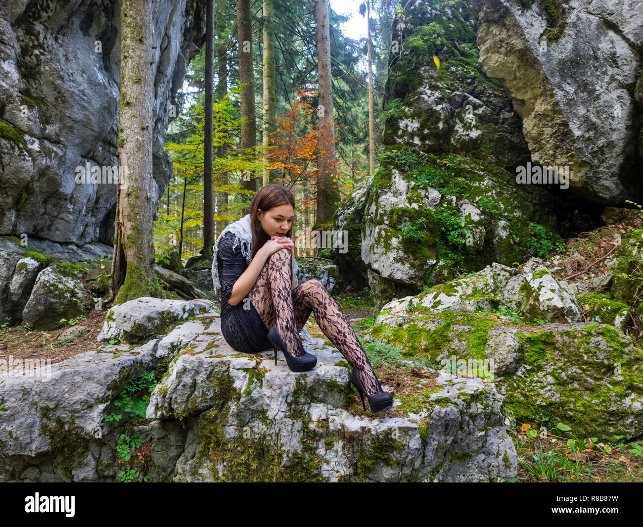 Beautiful young female in nature is sitting atop big rock thinking indifferent contemplating spike spiked thoughtful attentive minidress clothing Stock Photo
