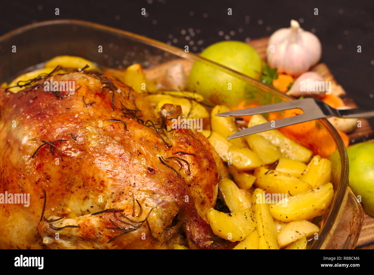 oven baked apple chicken in a glass dish on a wooden plank - Stock Image