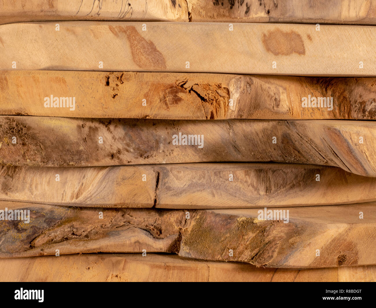 Stack of lying teak planks with a natural look and suitable for decorative applications or for further processing. - Stock Image