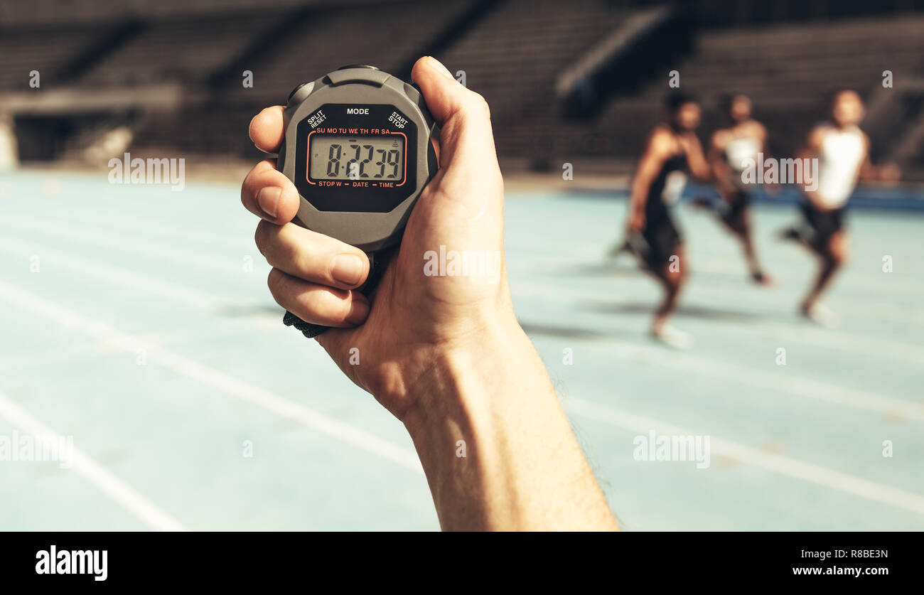 Close up of a hand holding a stop watch for time keeping at a running race. Athletes running a race while the time keeper measures time using a stop w - Stock Image