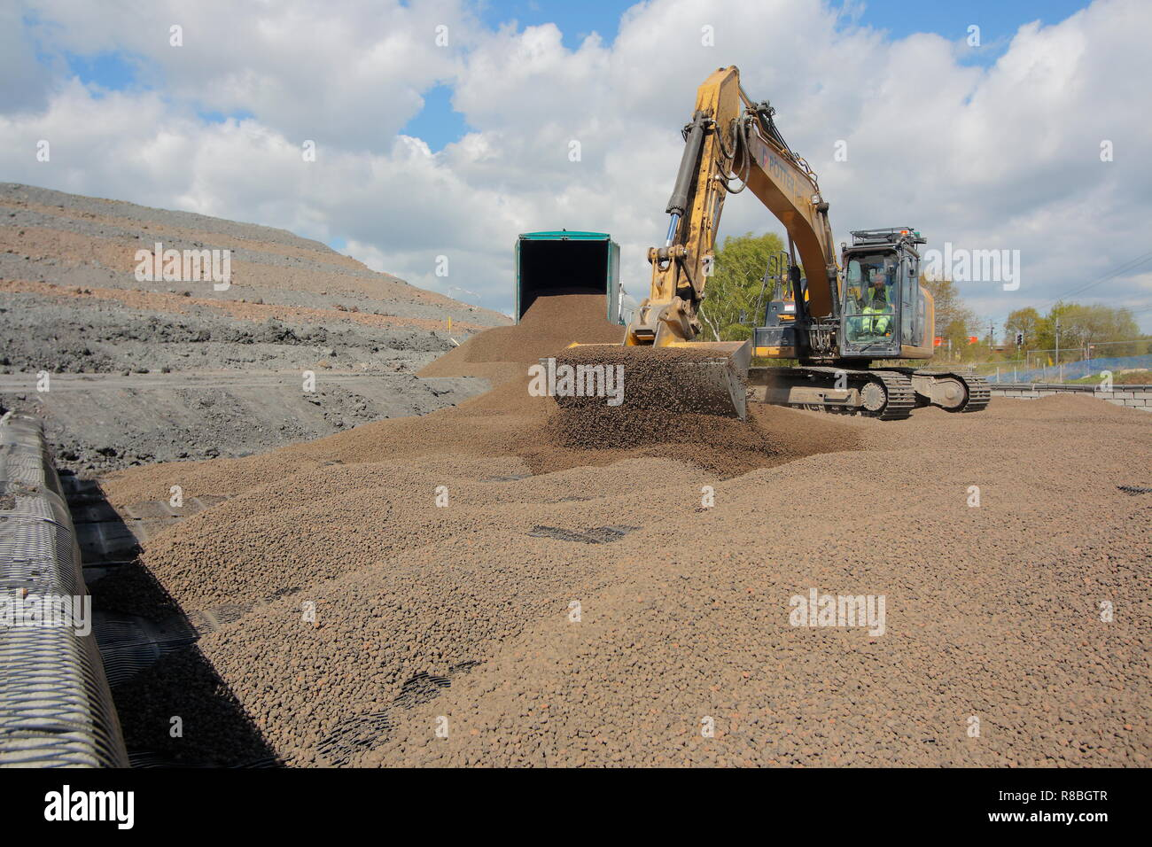 A Caterpillar 320E levelling out lightweight expanded clay aggregate , which is used for backfilling behind a railway bridge on the FARRRS link road. - Stock Image