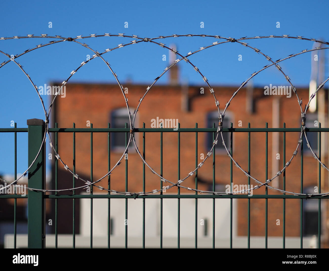 Green steel fence with barbed wire on top and red brick building in the background (out of focus) - Stock Image