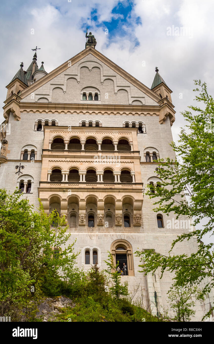 Great close low angle view of the beautiful west façade of the world famous Neuschwanstein Castle, a 19th-century Romanesque Revival palace at the... - Stock Image