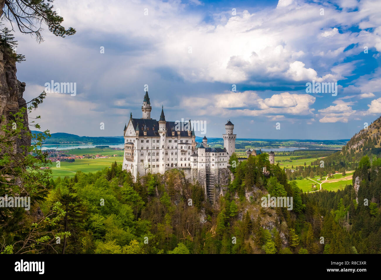 Panoramic view of the south façade of Neuschwanstein Castle surrounded by mountains. The popular tourist sight is a Romanesque Revival palace, built... - Stock Image