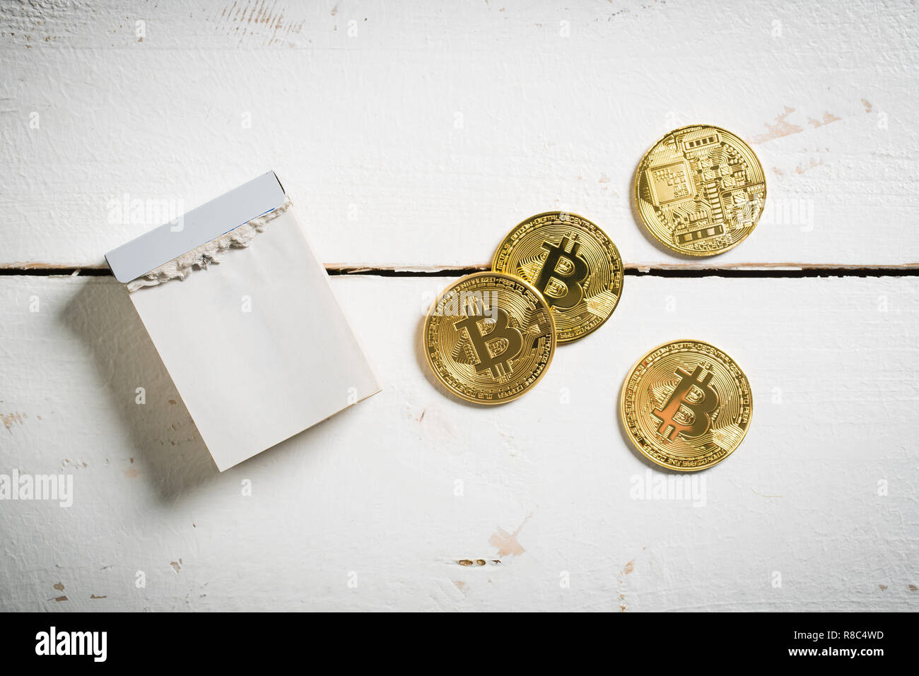 bitcoins with empty tear-off calendar on wooden background - Stock Image