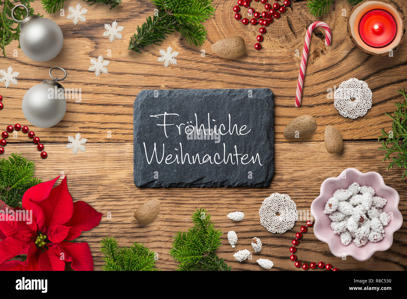 Christmas decoration on rustic wooden background and the German message for 'Merry Christmas!' - Stock Image
