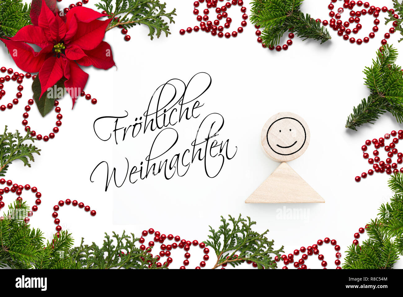 Christmas decoration and the German message for 'Merry Christmas!' on white background - Stock Image
