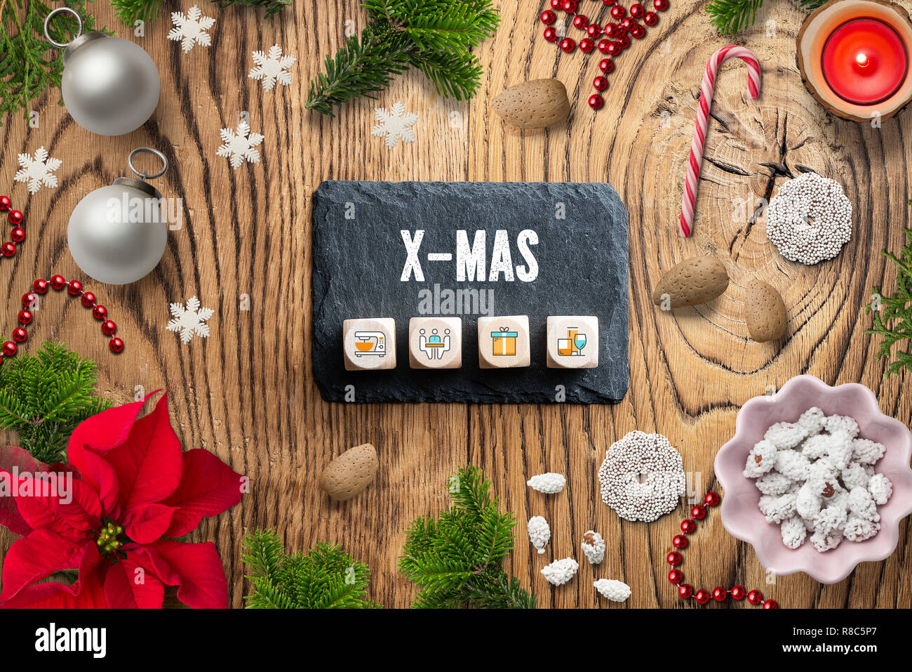 Christmas decoration on rustic wooden background and the message 'X-MAS' - Stock Image