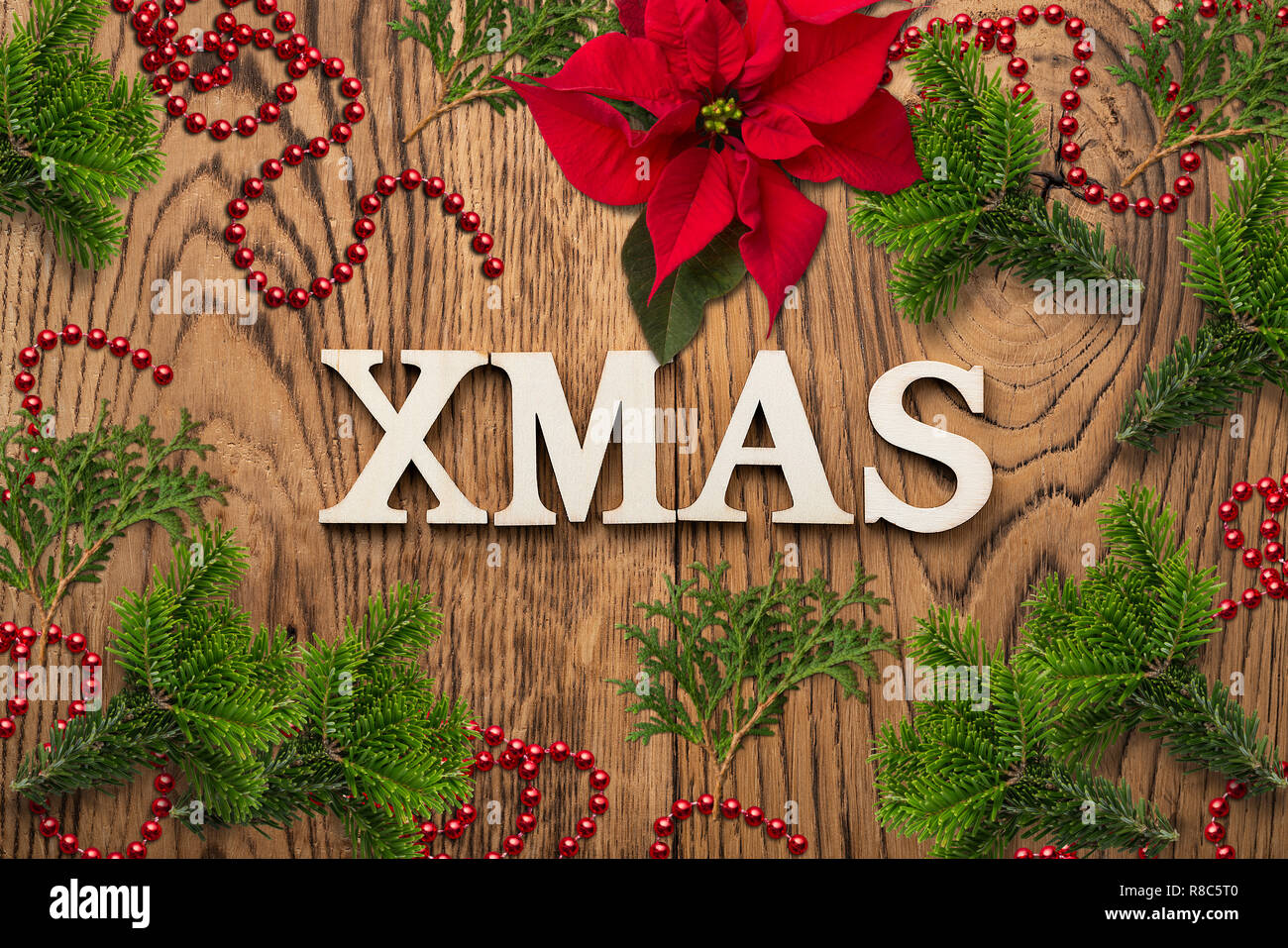 Christmas decoration on rustic wooden background and the message 'XMAS' - Stock Image