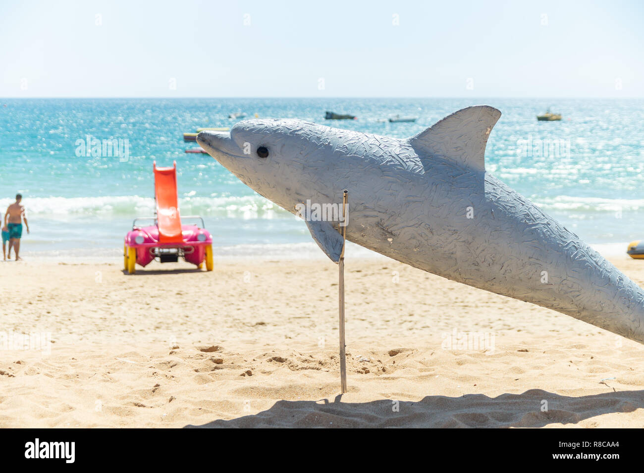 Dolphin sculpture indicating dolphin watch opportunity on the Albufeira beach, Algarve, Portugal - Stock Image