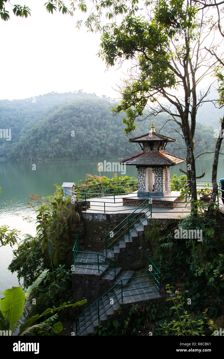 Green shore of lake Fewa, Pokhara. Small hindu temple and flowering trees. - Stock Image