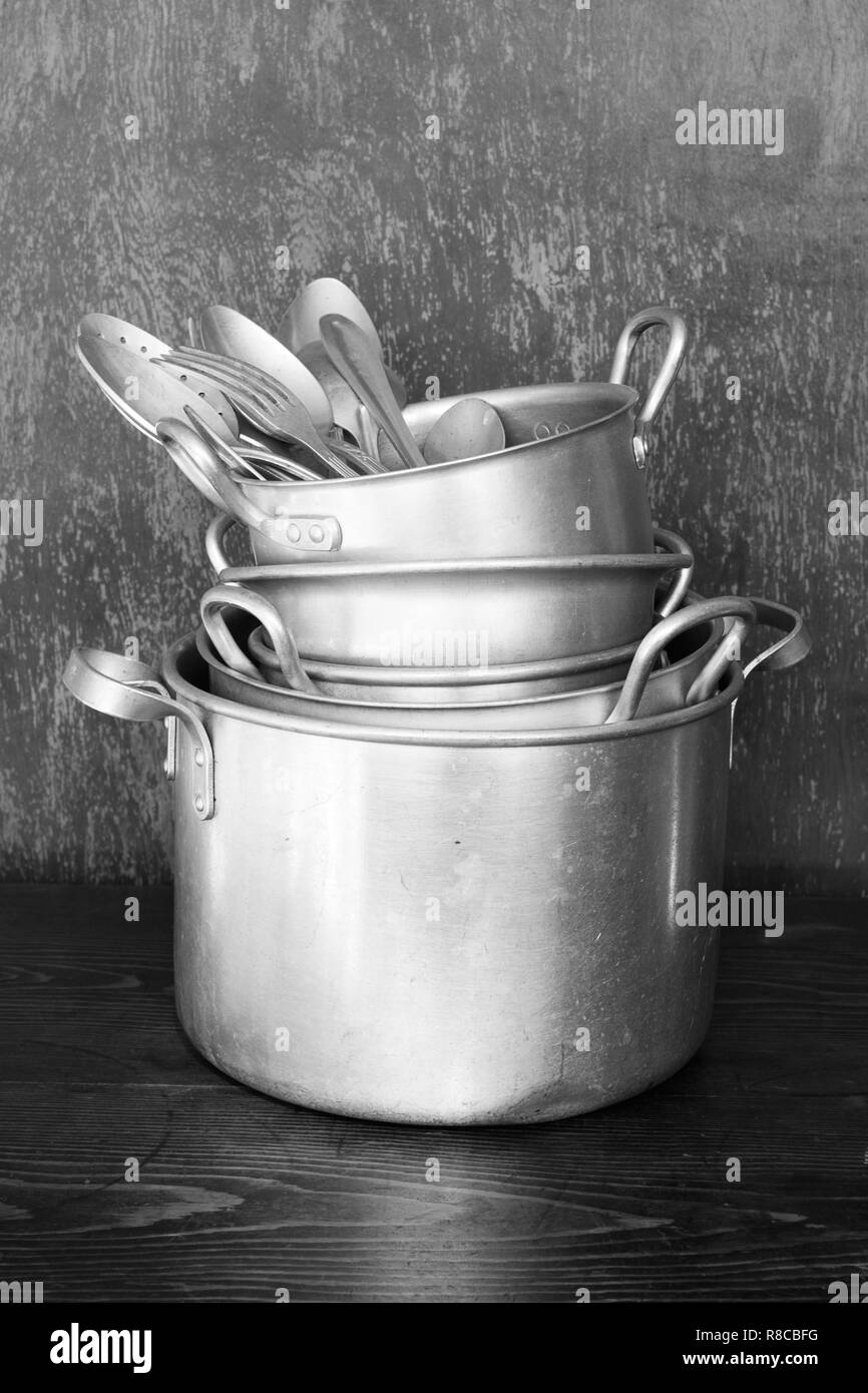 Old aluminum kitchen utensils are saucepans, dish, spoons, forks. Image black and white - Stock Image