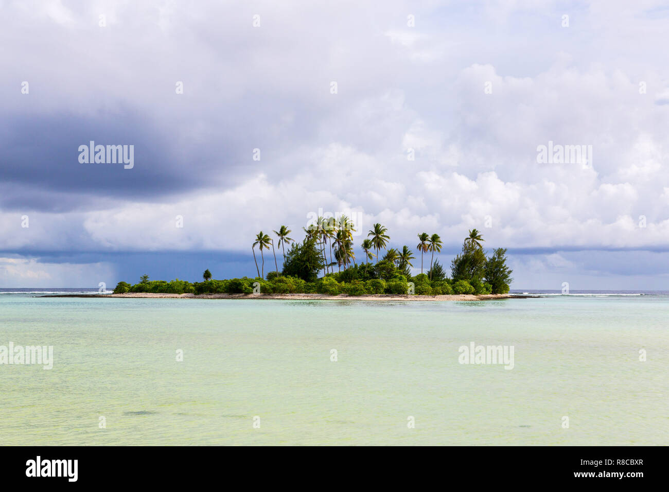 A small islet (motu) overgrown with palm forest somewhere in the lagoon of South Tarawa atoll in bad cloudy weather, Kiribati, Gilbert islands, Micron - Stock Image