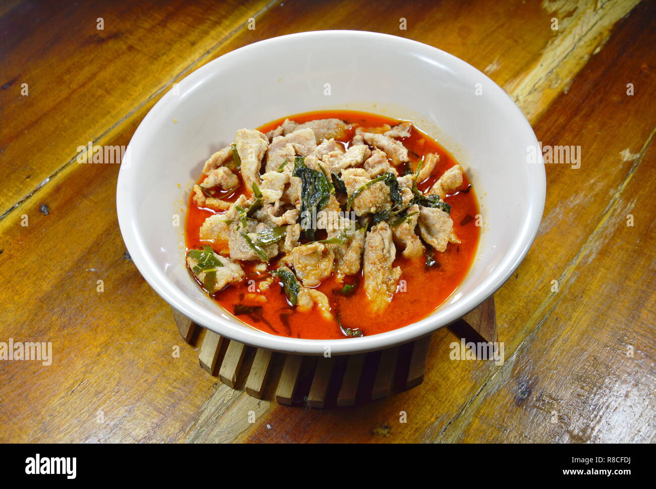 savory curry pork with coconut milk in bowl - Stock Image