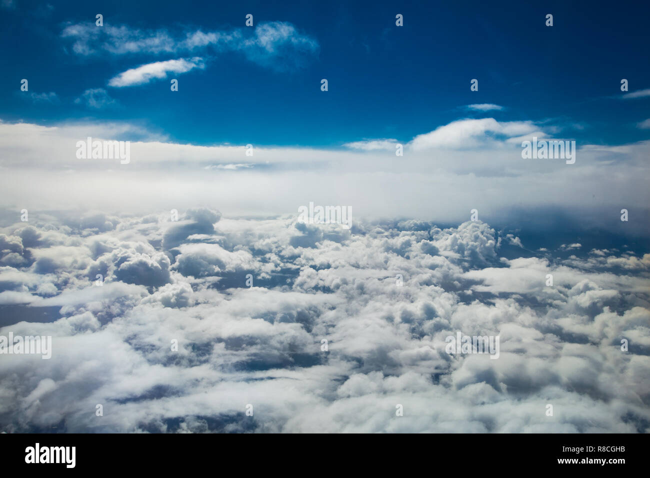 Aerial view White clouds in blue sky. Top view. View from the plane. Aerial bird's eye view. Aerial top view cloudscape. Texture of clouds. View from  Stock Photo