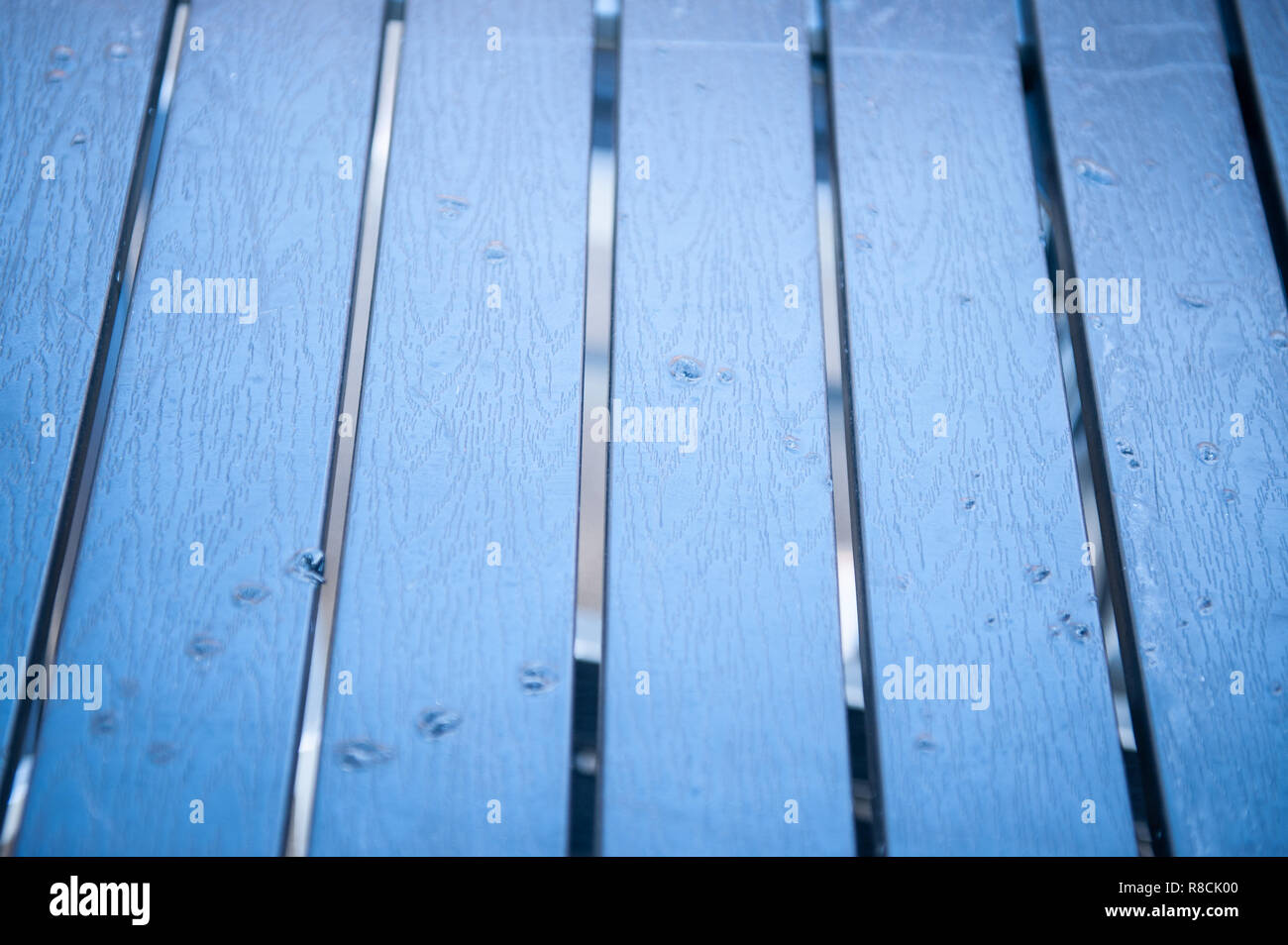 Blue Cafe table top with cigarette burns - Stock Image