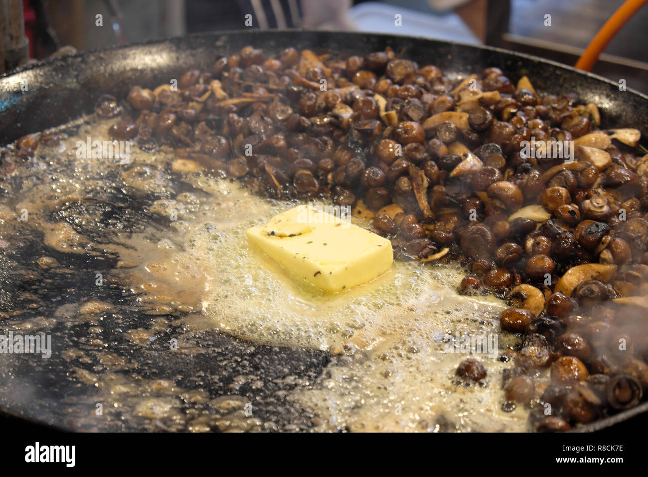 A block of butter sizzling on a cooker pan with wild mushrooms in preparation for making risotto at a Borough Market stall in London UK  KATHY DEWITT Stock Photo