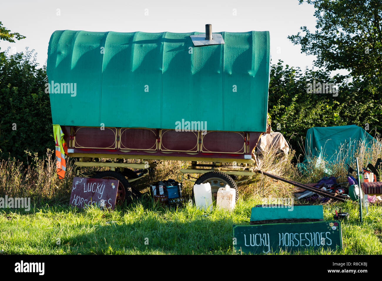 A horse-drawn caravan on a roadside verge in rural England with 'lucky horsehoes' signs. - Stock Image