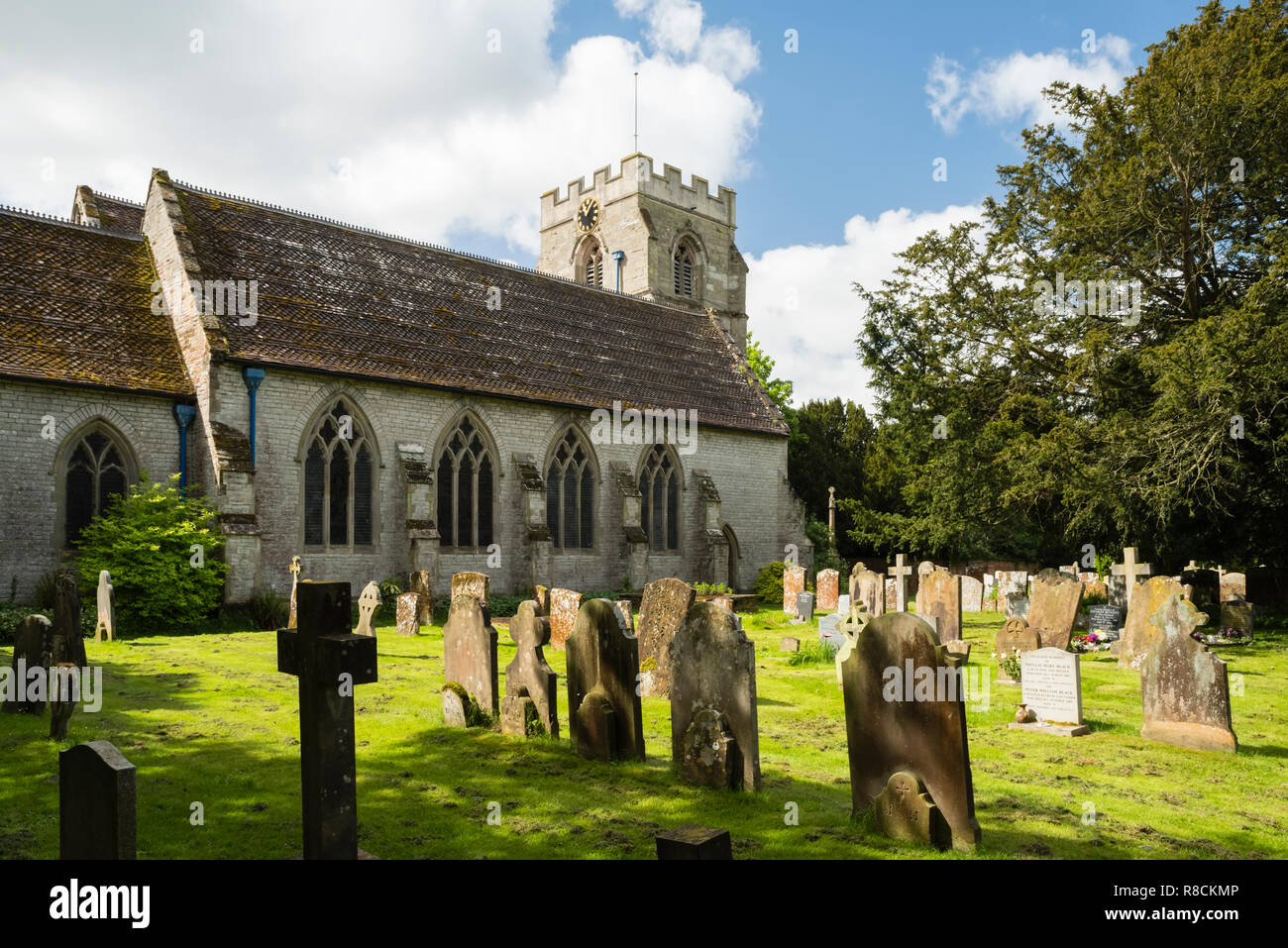 A quiet scene of medieval St. Peter's Church in the English village of  Wellesbourne, with the old gravestones in the foreground. - Stock Image