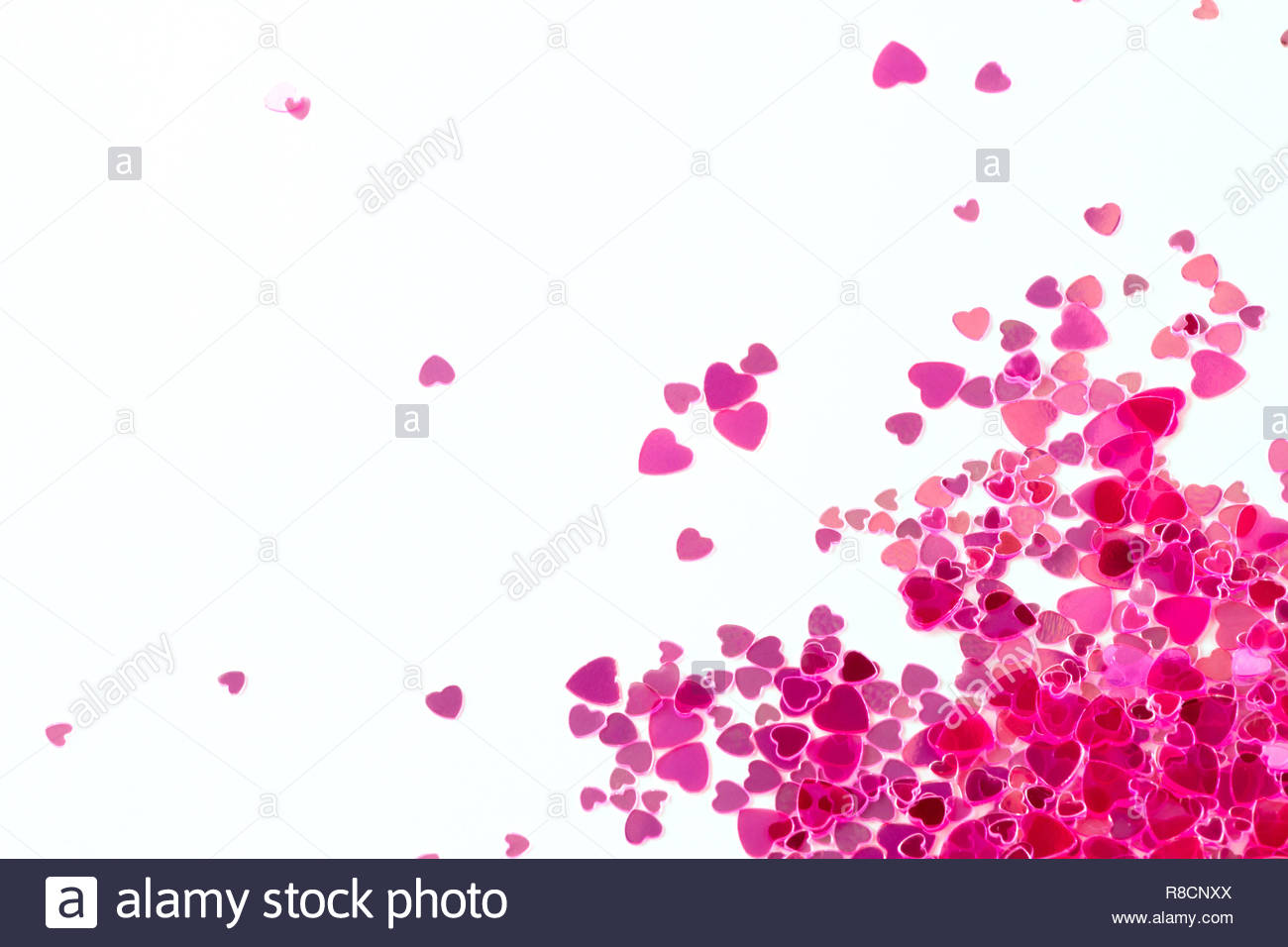 Pink sequins on a pink pastel background with confetti as asterisks. - Stock Image