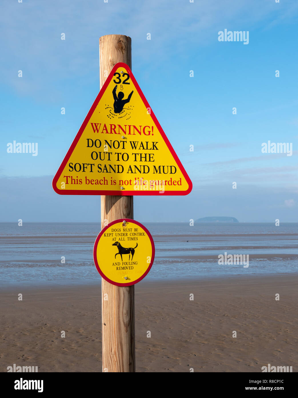 Yellow hazard triangle on Berrow Beach in Somerset UK warning about the treacherous soft mud at low tide and anti fouling message for dog owners - Stock Image