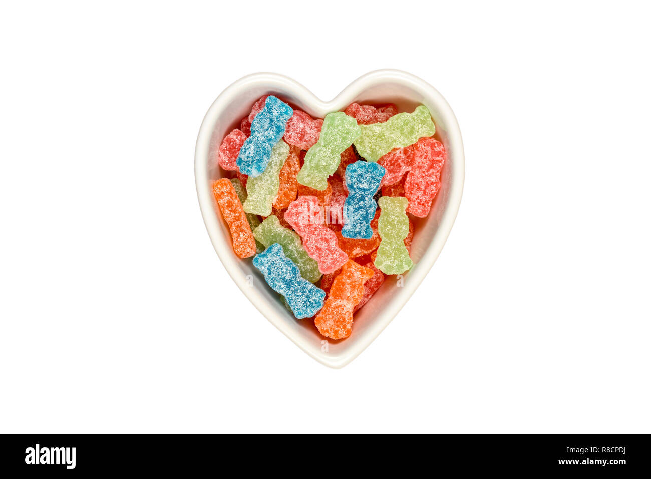 Variety of different color sweet and sour candy or sugar junk food in a heart shaped bowl  isolated on white with clipping path at ALL sizes. - Stock Image