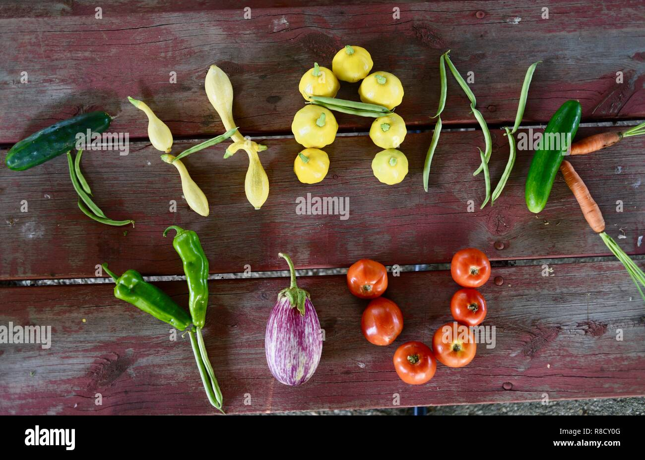 Organic vegetables and fruit spell out Thank You, for a healthy eating background focused on gratitude, on wooden picnic table. Top view. - Stock Image