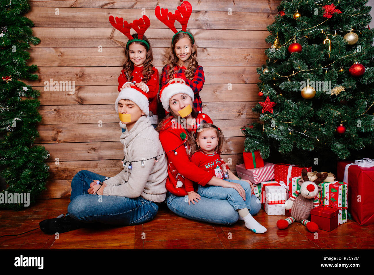 Bad Moms Christmas Kids.Bad Kids And Father And Mother Tied Up With Garland Near