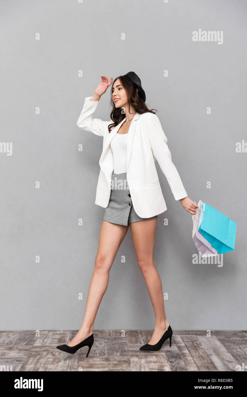 893114c84f5f Full length portrait of a smiling young woman dressed in mini skirt and  jacket over gray