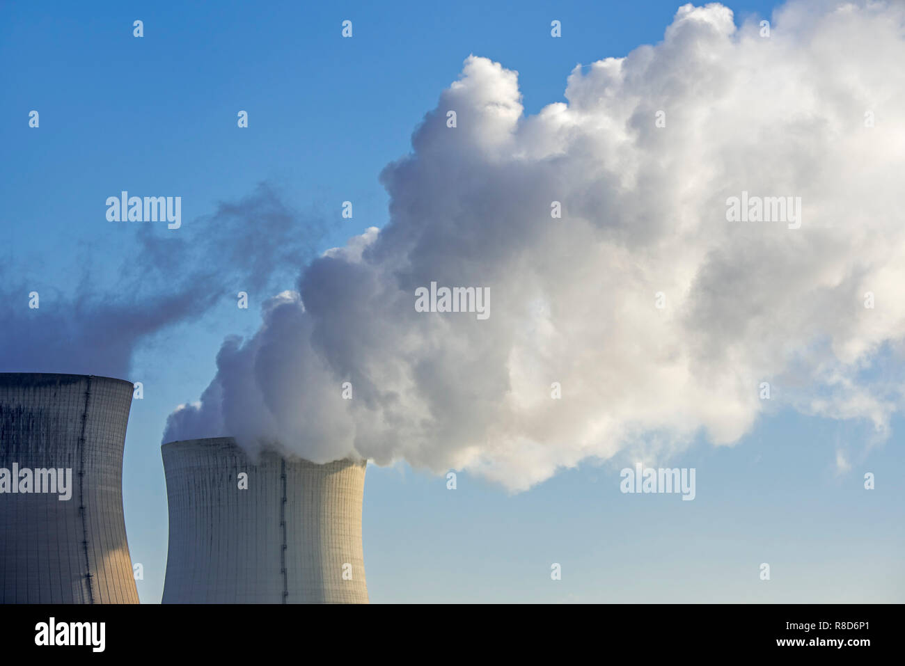 Two cooling towers of nuclear power station / nuclear power plant and massive cloud of water vapour / steam against blue sky - Stock Image