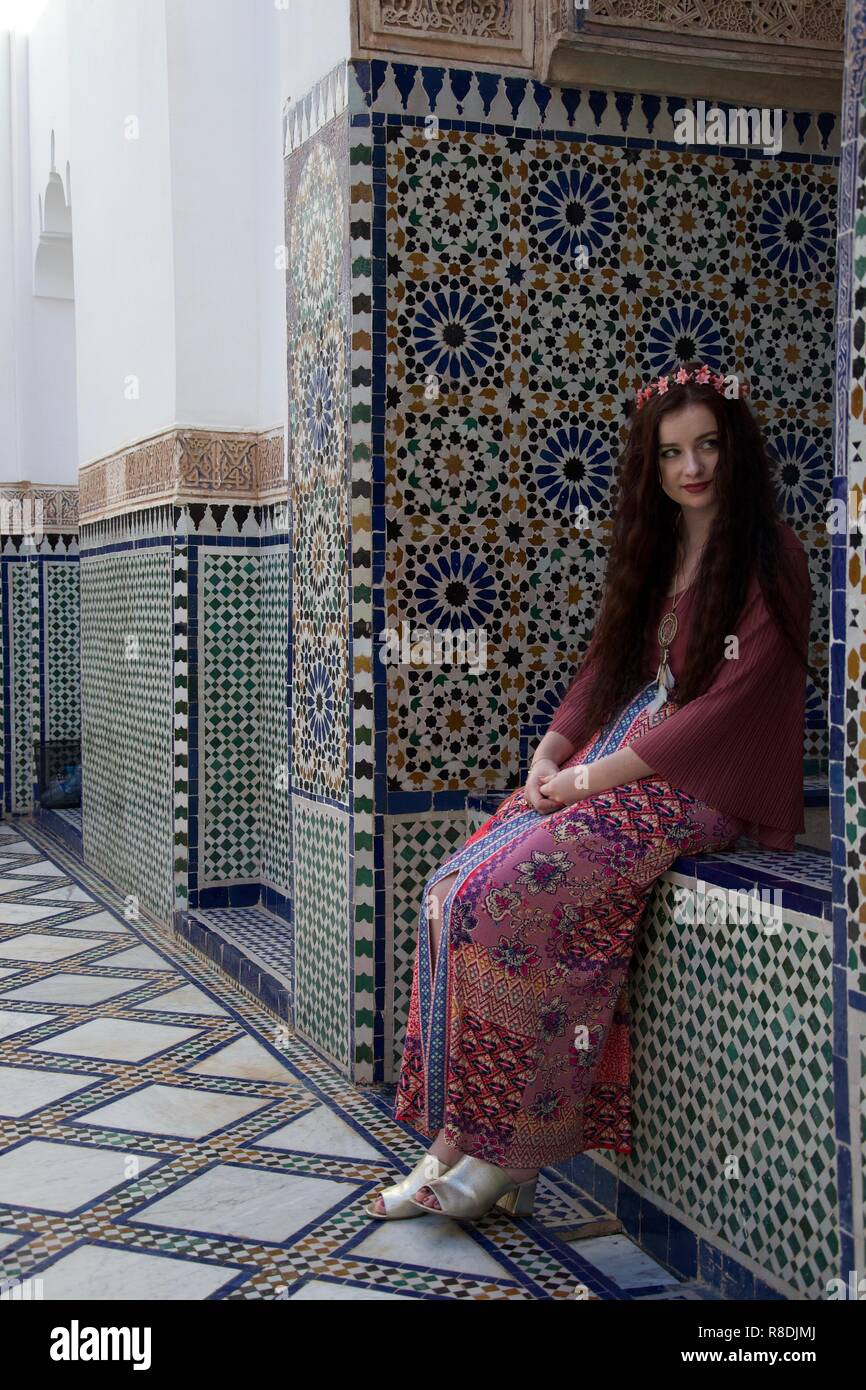 A hippie female causasian tourist with flowers in her hair sits in a Moroccan courtyard surrounded by elegant tiling - Stock Image